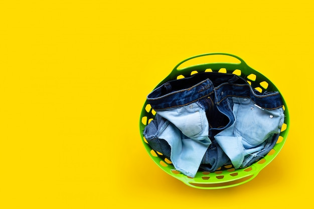 Jeans in green laundry basket on yellow