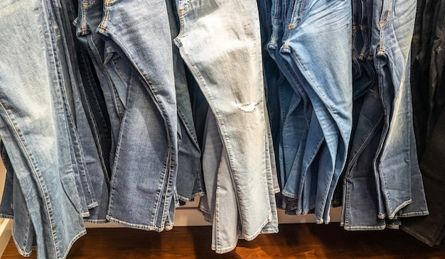 Jeans hanging on a rack. row of denim pants. concept of buy, sell , shopping and jeans fashion
