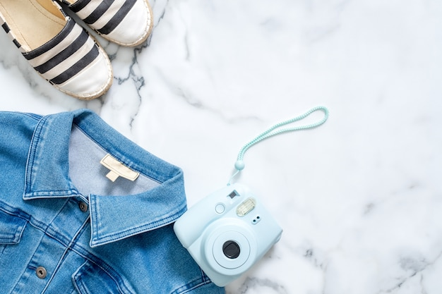 Jeans jacket, instant photo camera, striped summer sandals on marble background.