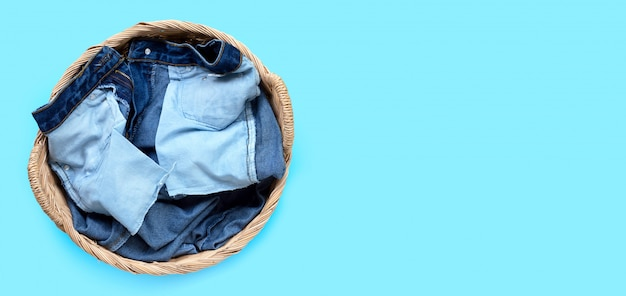 Jeans in laundry basket on blue background.