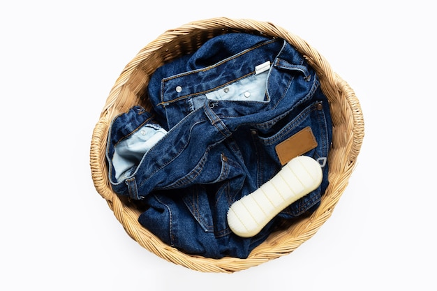 Jeans in laundry basket on white  surface. top view