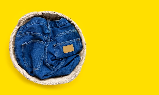 Jeans in laundry basket on yellow  background. top view