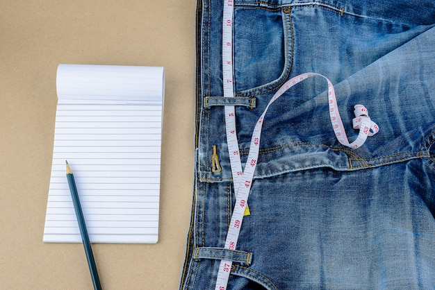 Jeans and measuring tape, notepad, pencil on wooden table