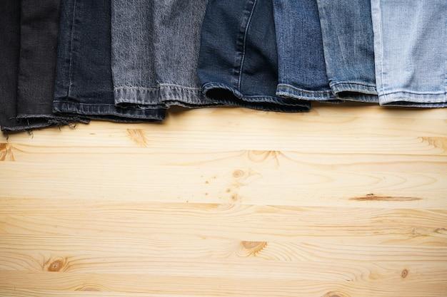 テキストのための木製のテーブルの場所のジーンズ、フラットレイ。