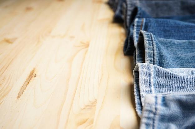テキスト用の木製テーブルスペースにジーンズ、フラットレイ。