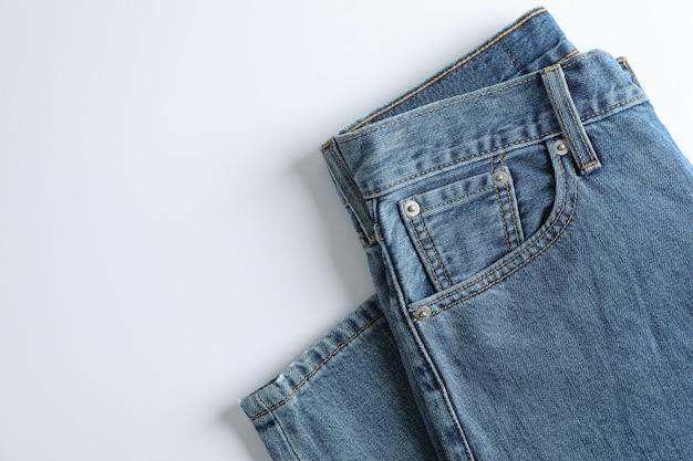 白いテーブルの上のジーンズ