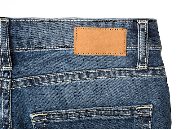 Jeans pants with back pocket and brown leather tagold wooden background