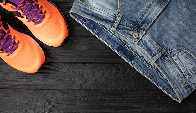 Jeans and sneakers flat view on wooden background