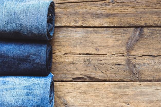 木製の背景に積み上げジーンズ