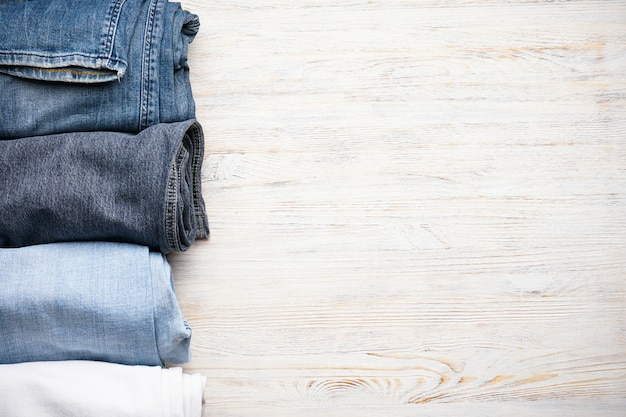 木製のテーブルに積み上げられたジーンズ、上面図。テキスト用のスペース。