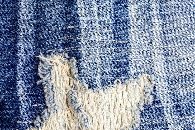 Jeans torn denim texture surface.
