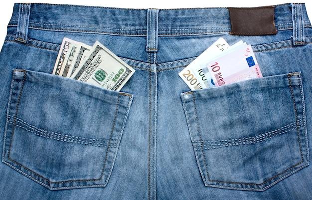ポケットに異なる通貨を持っているジーンズ-ユーロとドルのバランスの象徴