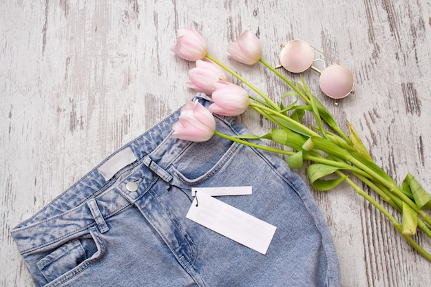 Jeans with a clean tag, pink glasses and tulips