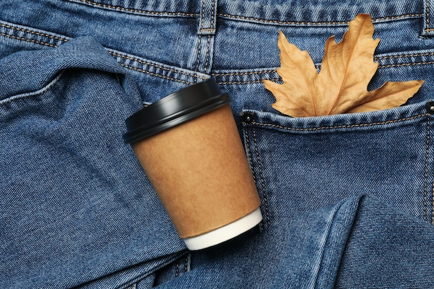 Jeans with leaf in pocket and paper cup, space for text