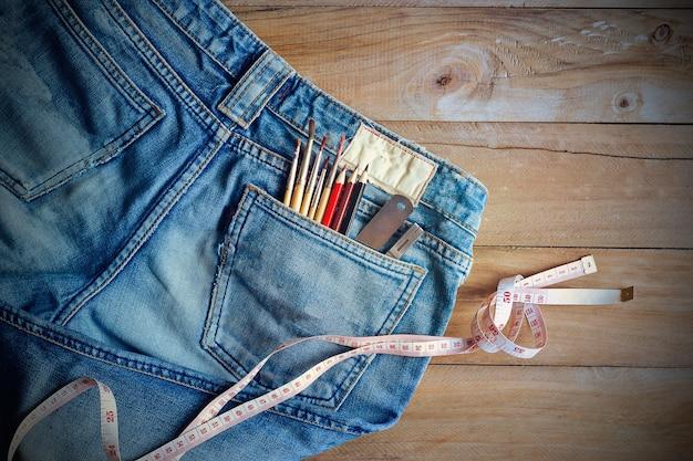 Джинсы с мерилом и цветными карандашами, кисти в заднем кармане на деревянных