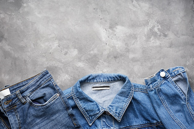 Jeans women's jacket and denim pants over gray  , top view. place for text.
