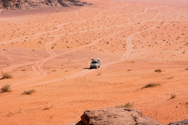 Jeep safari in wadi rum desert, jordan. tourists in the car ride on off-road on the sand among the rocks