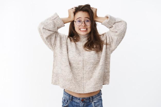 うわあ、困っています。歯を食いしばって、絶望して頭に手をつないで、厄介な状況を抱えているとして神経質で不安を感じている、心配してびっくりした若い女性の肖像画。コピースペース