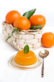 バスケットの葉とゼリーと新鮮なオレンジ色のマンダリン