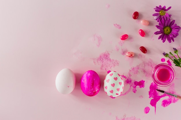 Jelly beans and flowers near eggs