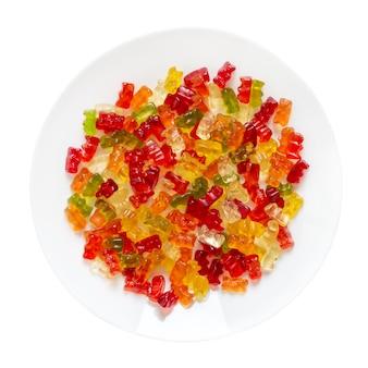 흰색 배경에 고립 된 접시에 젤리 곰. 전통 과일 구미. 평면도.
