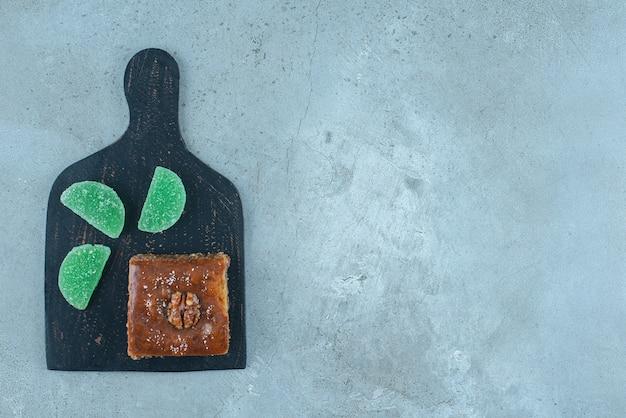 Желейные конфеты и пахлава на черной доске на мраморной поверхности