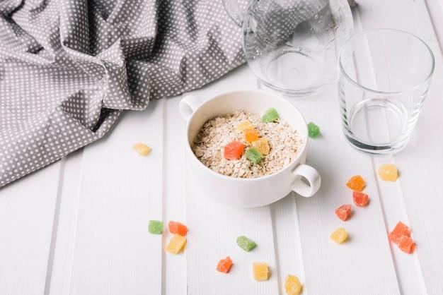 Caramelle di gelatina nella ciotola di avena sul tavolo bianco