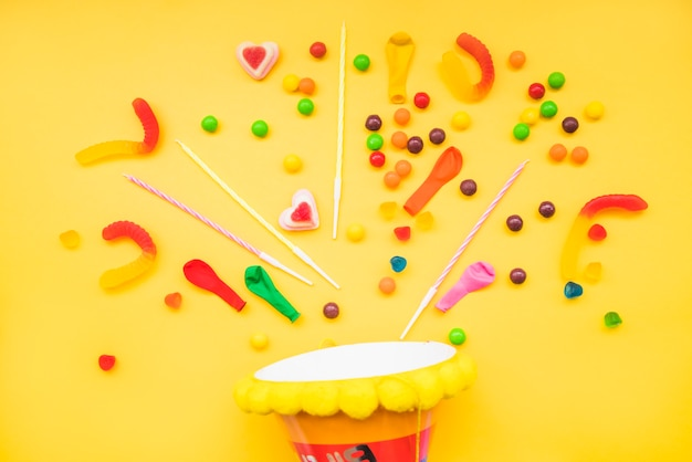 Jelly candies and candles over the party hat against yellow background