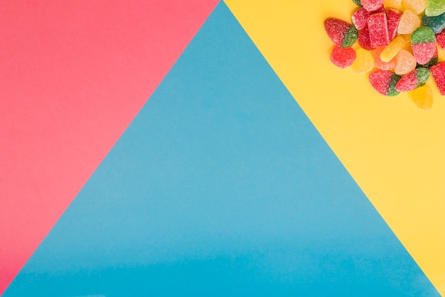 Jelly candies on colorful triangular background