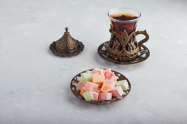 Jelly candies served with a glass of tea on white surface.