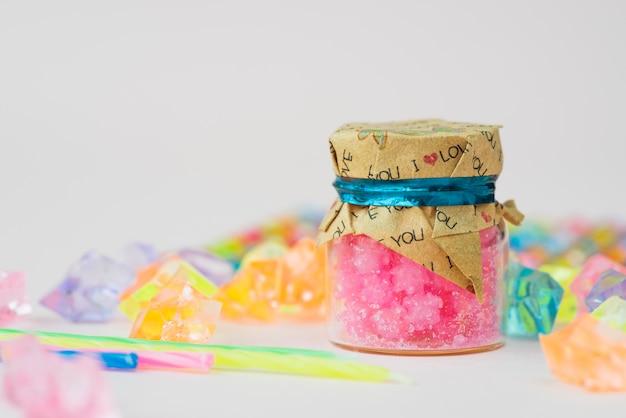 Cera della candela di gelatina in bottiglia con le perle variopinte su priorità bassa bianca