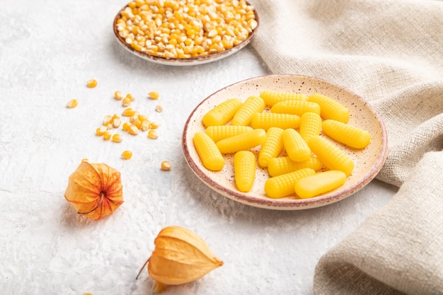 Jelly corn candies on gray concrete background and linen textile
