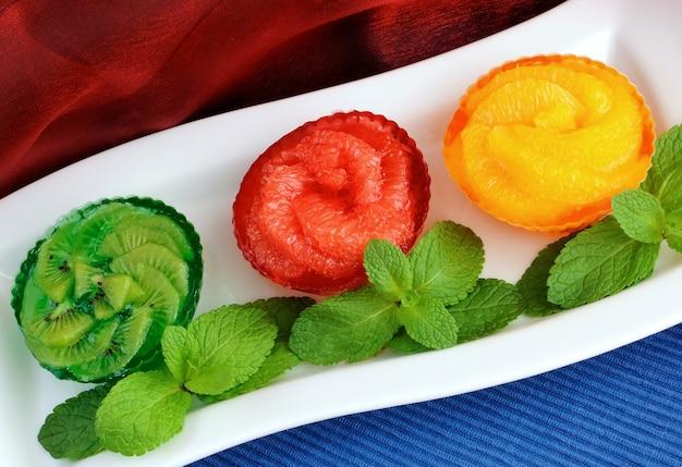 민트를 곁들인 신선한 과일(오렌지, 자몽, 키위)의 젤리 디저트
