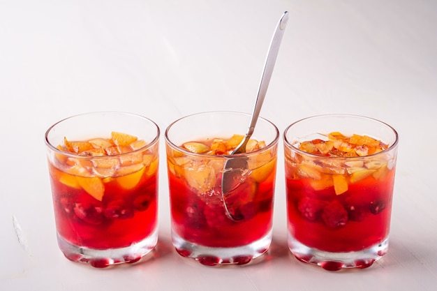 Jelly dessert with fruits apricot raspberry in three drinking glasses with single spoon yellow red summer white surface isolated in row