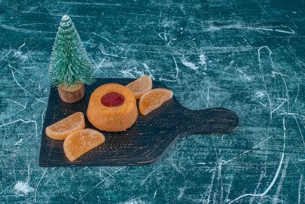 青い背景の黒板にゼリーで満たされたケーキ、マーマレードと木の置物。高品質の写真