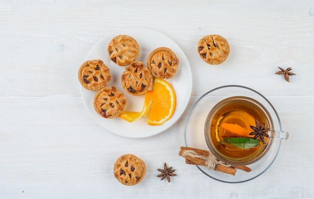 Желейные торты и апельсин в тарелке с корицей и чашка чая