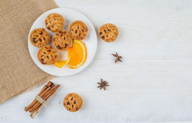 Jelly filling cakes and orange in a plate with cinnamon and a placemat