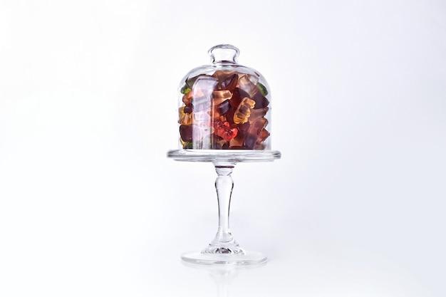 Мармелады желе внутри стеклянной чашки с крышкой.