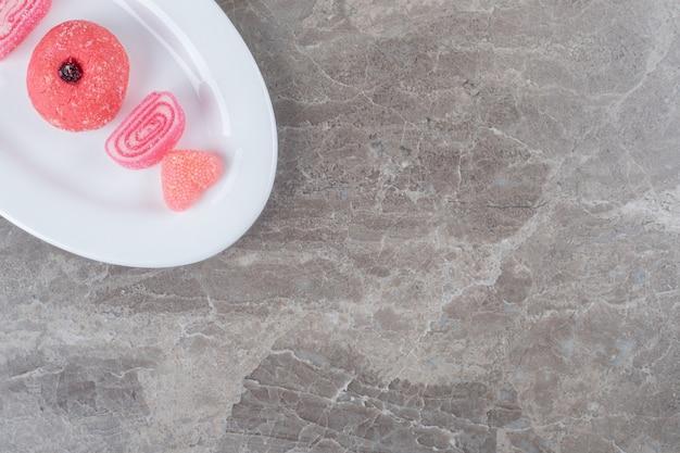 大理石の表面の大皿に並べられたゼリー菓子とクッキー