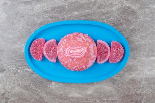 大理石の表面の大皿に配置されたゼリー菓子とクッキー