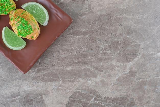 Желейные конфеты и булочки с зеленой начинкой на блюде на мраморной поверхности