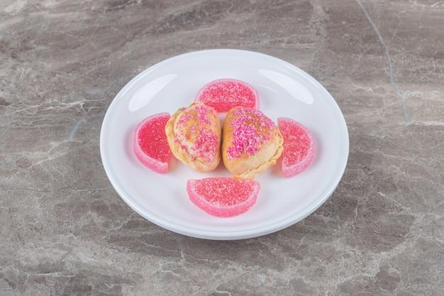 Желейные конфеты и булочки с ореховой начинкой на блюде на мраморной поверхности