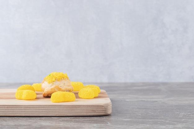 大理石の表面にレモン風味の粉末をトッピングした小さなお団子の周りのゼリー菓子