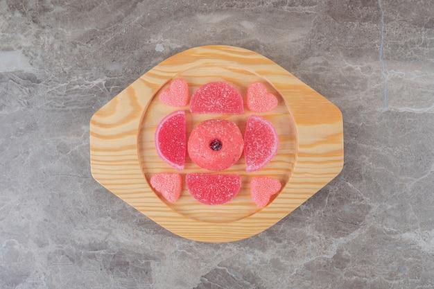 Желейные конфеты вокруг небольшого пончика на деревянном блюде на мраморной поверхности