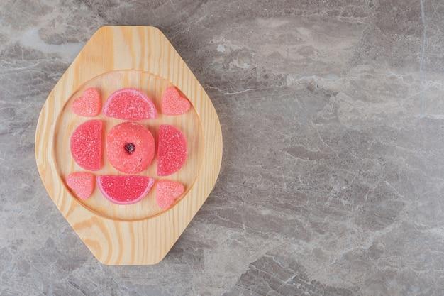 Caramelle gommose intorno a una piccola ciambella su un piatto di legno su una superficie di marmo