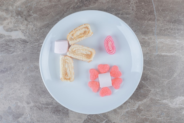 Caramelle gommose, marshmallow e fette di rotolo di torta su un piatto da portata su una superficie di marmo