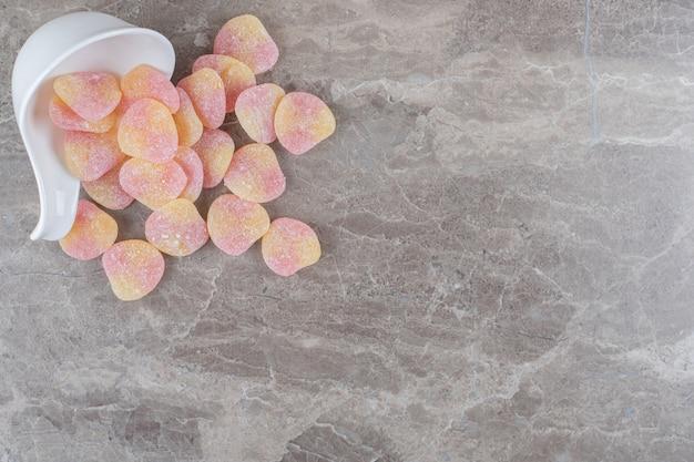 Caramelle gommose fuoriuscite da una piccola ciotola sulla superficie di marmo