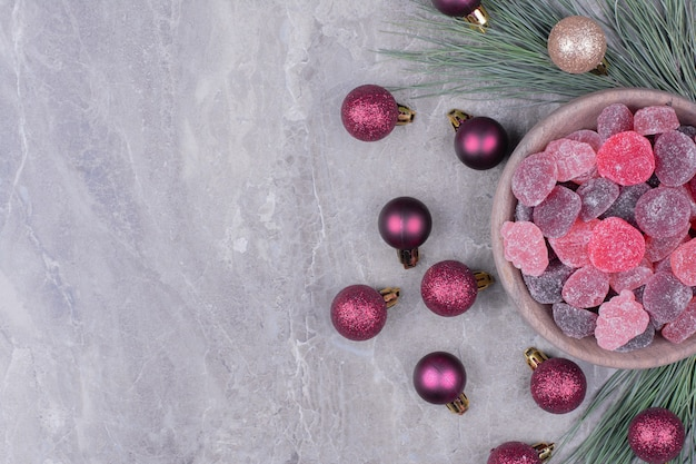 Jellybeans in a wooden cup with glittering balls around Free Photo