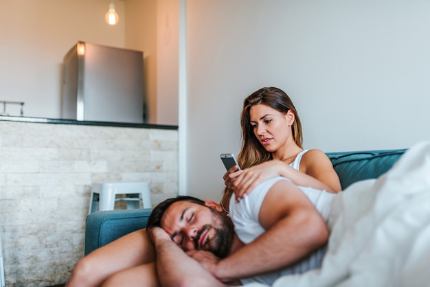 Jelous young woman cheking boyfriend's phone while he sleeps.