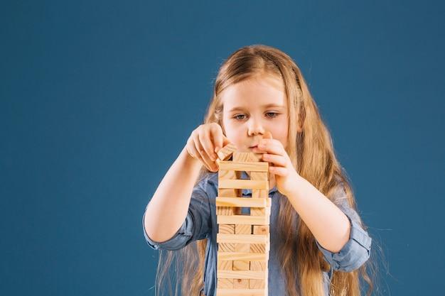 Jengaタワーを構築する焦点を絞った少女
